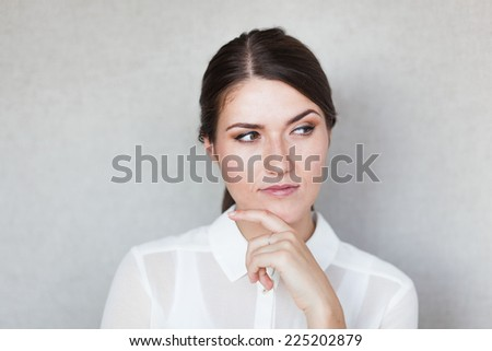 Closeup portrait of pretty mad young woman, finger on lips, daydreaming something serious and upsetting. Human facial expressions, emotions, feelings, signs, symbols - stock photo