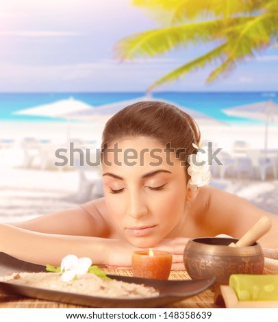 Closeup portrait of pretty woman lying down on massage table on the beach, closed eyes, luxury spa resort, tropical vacation, summer holidays - stock photo