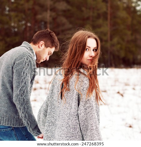 Closeup portrait of pretty young beautiful couple in love walking together on snow cold forest field  - stock photo