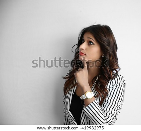 Closeup portrait of pretty young indian business woman thinking hand on chin looking up having an idea, isolated on white background. - stock photo