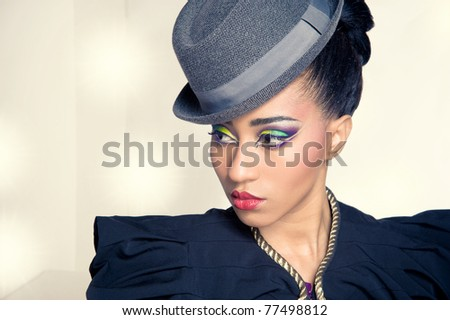 Closeup portrait of pretty young showgirl wearing a hat, with stage lights on background - stock photo