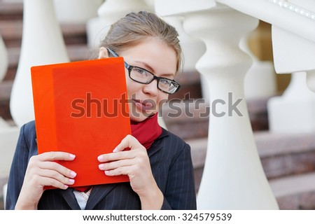 Closeup portrait of pretty young student girl holding exercise books and folder. - stock photo