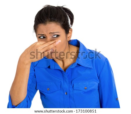 Closeup portrait of pretty young woman closing covering nose, something stinks, isolated on white background. Negative facial expressions, emotions, feelings, reaction, attitude, behavior, perception - stock photo