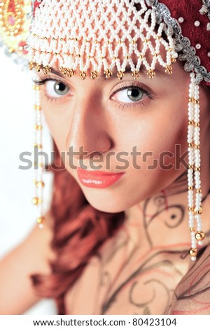 Closeup portrait of pretty young woman with red hairs posing near wall smiling and wearing beautiful headwear - kokoshnik of russian traditional clothing.