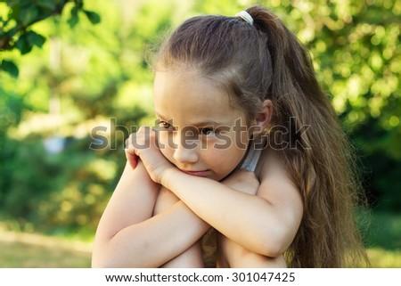 Closeup portrait of sad cute little girl at sunset. Domestic violence concept.  - stock photo