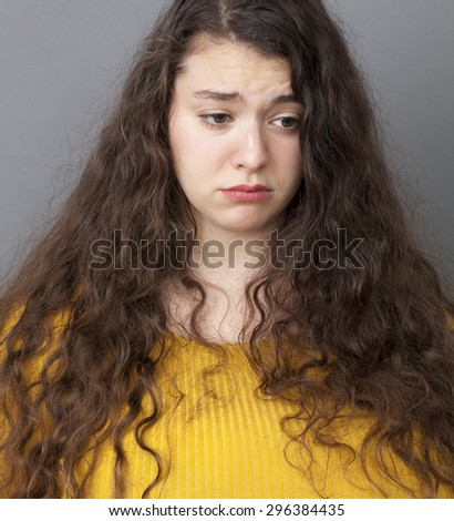 closeup portrait of sad 20's woman with long brown hair looking depressed, ready to cry, studio shot - stock photo