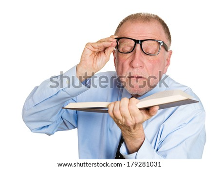 Closeup portrait of senior male mature man with trouble, problems reading book because of vision problems, isolated on white background. Emotions, facial expressions. Geriatric aging health issues - stock photo