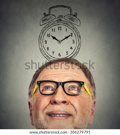 Closeup portrait of senior man with glasses and alarm clock above his head looking up thinking isolated on gray wall background - stock photo