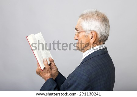 Closeup portrait of senior man with glasses standing and reading a book over gray background - stock photo