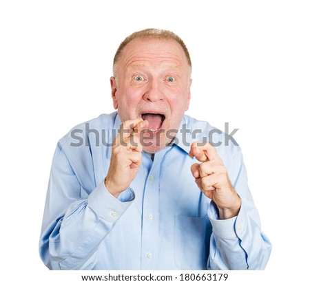 Closeup portrait of senior mature man crossing fingers wishing and praying for miracle, hoping for the best, isolated on white background. Positive human emotion facial expression feelings attitude