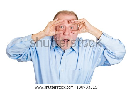 Closeup portrait of senior mature serious man peeking through his fingers like binoculars, looking to the future at the camera, shocked by what he sees, isolated on a white background. Sign, symbols - stock photo
