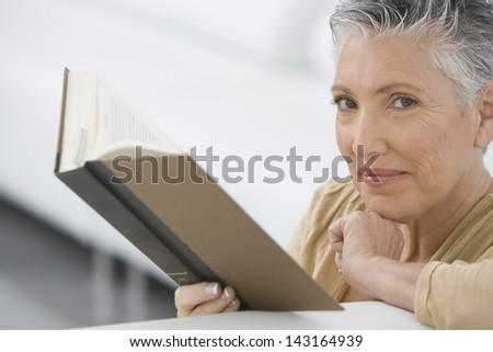 Closeup portrait of senior woman reading book on sofa - stock photo