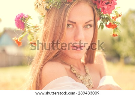 closeup portrait of sensual blonde young pretty lady wearing flower crown having fun relaxing enjoying summer & looking at camera on green outdoors copy space background - stock photo