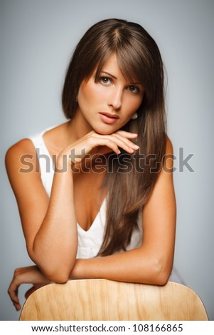 Closeup portrait of sensual female in beige dress leaning on her elbow. Shallow deep of field. - stock photo