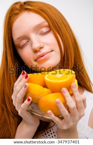 Closeup portrait of sensual tender attractive pretty young woman with eyes closed holding glass bowl with oranges - stock photo