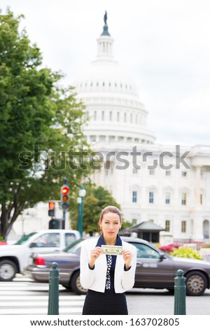 Closeup portrait of serious, quiet, corrupt politician in washington dc, holding dollar bills isolated on Capitol building background. Human emotions and facial expressions. Greed, politics concept - stock photo