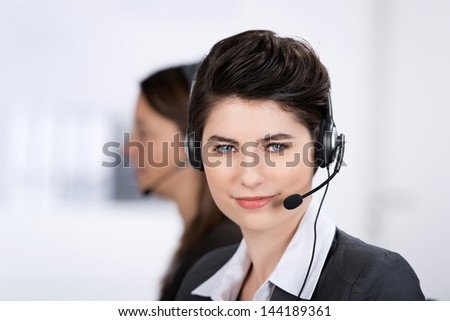 Closeup portrait of serious young female customer service executive wearing headset with coworker in background at office