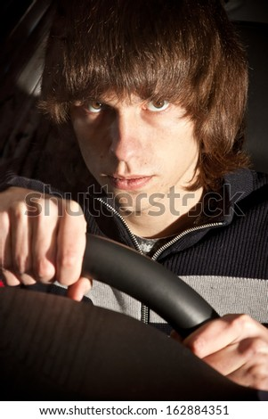 Closeup portrait of serious young man holding steering wheel on drivers seat  - stock photo
