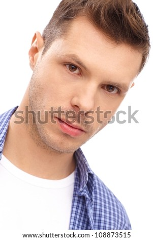 Closeup portrait of serious young man with trendy hairstyle.