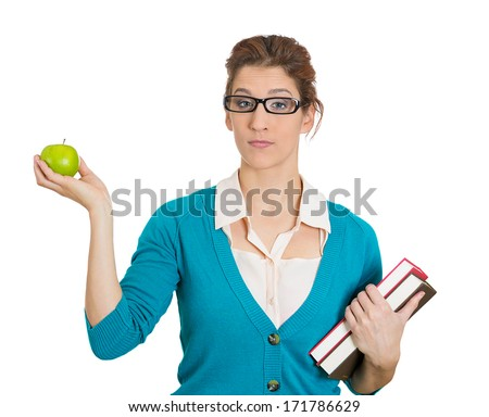 Closeup portrait of serious young woman student or teacher with eyeglasses holding books in one arm and green apple in other hand, isolated on white background. Diet, exercise and school work balance - stock photo