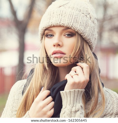 Closeup portrait of sexy blonde girl in knitted clothes. Looking at camera. Outdoors - stock photo