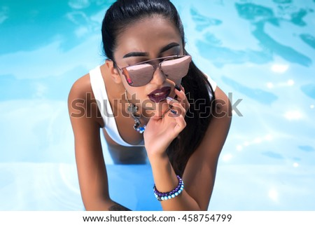closeup portrait of sexy hot beautiful girl model with dark hair with bright makeup,red lips posing in swimming pool.young woman beauty portrait in water.beautiful long hair female posing in the pool  - stock photo