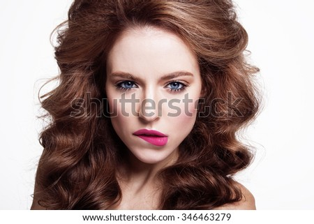 Closeup portrait of sexy young beauty girl with blue eyes. Nude makeup with perfect clean skin with colourfull pink lips and curly hair.