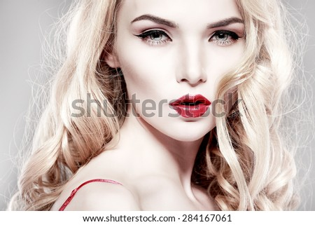 Closeup portrait of sexy  young woman with beautiful blue eyes and red lips on a grey background - stock photo