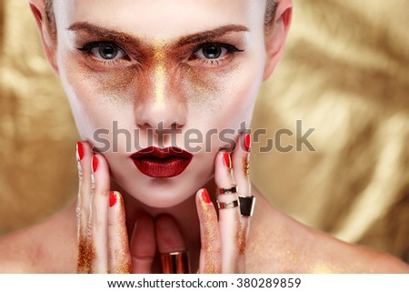 Closeup portrait of sexy  young woman with beautiful blue eyes and red lips on gold  background - stock photo