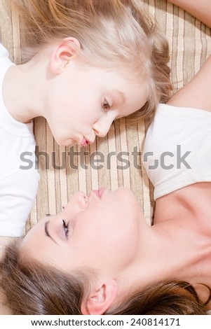 closeup portrait of showing kiss young pretty lady and child blond girl, lying face to face  - stock photo