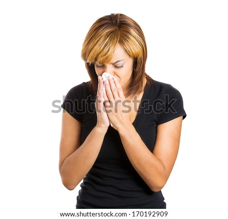 Closeup portrait of sick young woman student or worker with allergy or germs cold, blowing her nose with kleenex, looking miserable unwell very sick, isolated on white background. Flu season, vaccine - stock photo