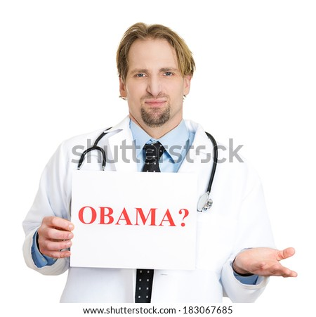 """Closeup portrait of skeptical male healthcare professional or doctor or nurse with stethoscope holding up a sign which says """"Obama?"""", isolated on white background. Approval rating at an all-time low - stock photo"""