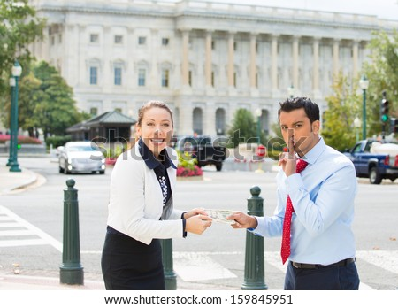 Closeup portrait of sleazy businessman or lobbyist offering money dollars bribe and saying shhh to happy corrupt politician in washington dc, isolated on Capitol building background - stock photo