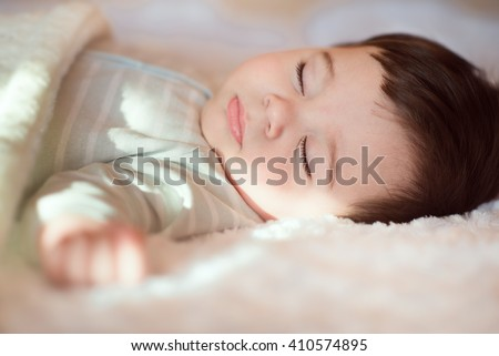 Closeup portrait of sleeping baby covered with knitted blanket