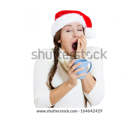 Closeup portrait of sleepy young cute christmas girl, attractive woman, tired, yawning holding cup of hot beverage, wearing Santa Claus hat, isolated on white background. Busy holiday season concept. - stock photo