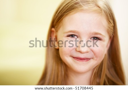 closeup portrait of smilig little girl indoor; shallow DOF, focus on eyes - stock photo