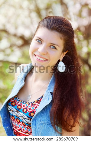 Closeup portrait of smiling beautiful sexy Caucasian adult girl woman with long dark red brown hair and blue eyes in tshirt with folk motifs and jeans vest with silver round drop earring - stock photo