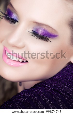 closeup portrait of smiling beautiful woman with long eyelashes and metallic purple violet eyeshadows - stock photo