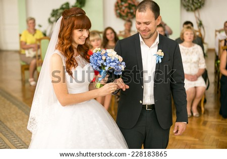 Closeup portrait of smiling bride and groom changing with wedding rings - stock photo