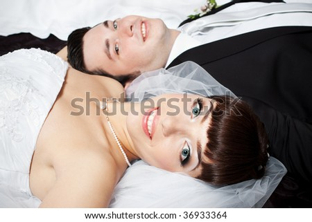 Closeup portrait of smiling bride lying with blurred groom face in the background