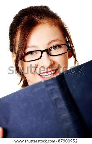 Closeup portrait of smiling, caucasian, teen student with a blue book over white. - stock photo