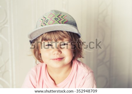 Closeup portrait of smiling cute Caucasian blond baby girl in gray cap, warm vintage tonal correction photo filter - stock photo