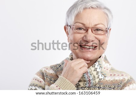 Closeup portrait of smiling elderly woman in glasses. - stock photo