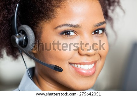Closeup portrait of smiling female customer service representative wearing headset in office - stock photo