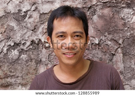 closeup portrait of smiling good-looking gorgeous man standing against an old wall background. - stock photo