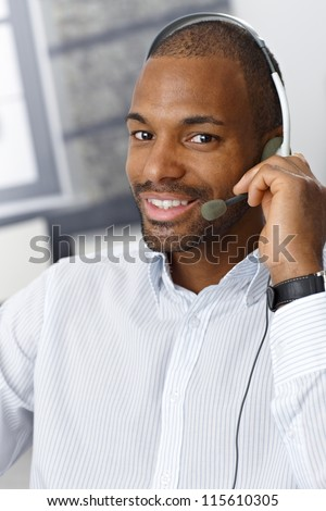 Closeup portrait of smiling handsome Afro-American customer service representative working with headset. - stock photo