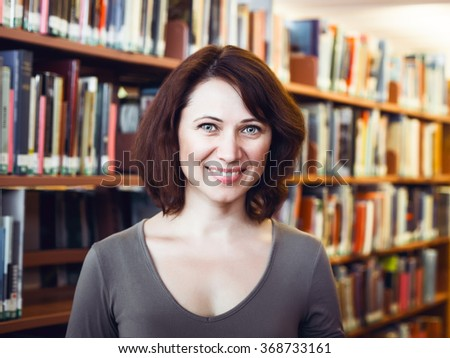 Closeup portrait of smiling happy  middle age mature woman student in library looking directly in camera, teacher librarian profession, back to school concept - stock photo