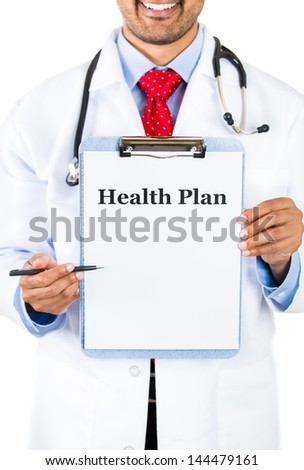 Closeup portrait of smiling health care professional with stethoscope and red tie, holding a sign which says health plan and showing space for text with pen, isolated on white background