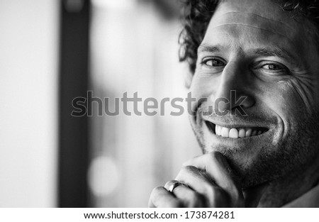 Closeup portrait of smiling male doctor with hand on chin - stock photo
