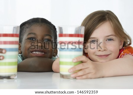 Closeup portrait of smiling multiethnic kids at table with glasses - stock photo